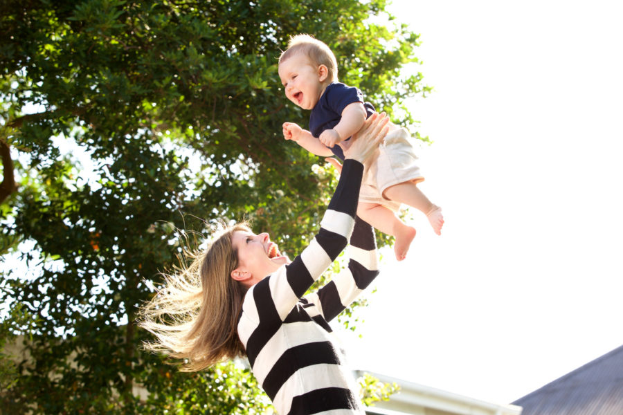 mother taking her baby outside and throwing the baby into the air