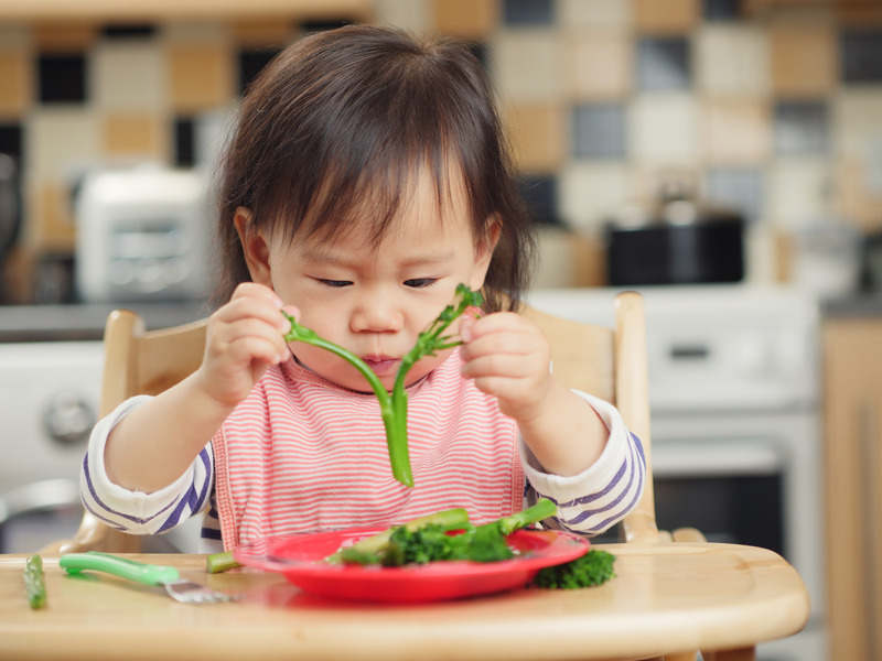 chinese baby eating asparagus