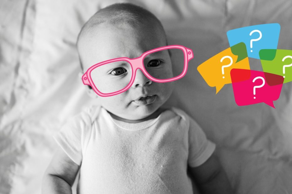 black and white photo of baby wearing glasses looking at colorful question marks